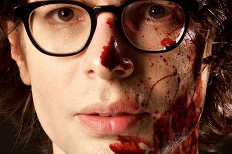 Simon Amstell with blood on his face to promote his film Carnage